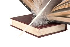 stack of books and quill - stock photo