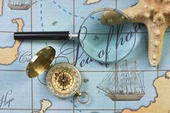 Magnifier and compass on  map Stock Photos