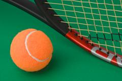 tennis racket and  ball on green background - stock photo