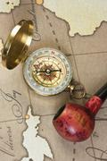 Tobacco pipe and compass on map Stock Photos