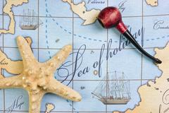 Stock Photo of tobacco pipe and  starfish on map