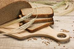 slices of rye bread and ears of corn on a wooden table - stock photo