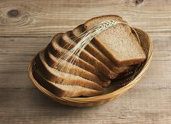 Slices of rye bread and ears of corn in basket Stock Photos