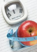 Apple and measuring tape on the floor scales Stock Photos