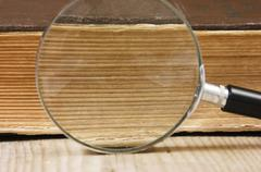 Old book and magnifying glass Stock Photos