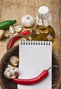 notebook for cooking recipes and vegetables on  cutting board - stock photo