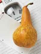 pear and a note on floor scales - stock photo