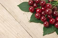 Stock Photo of berry cherry with leaves on wooden background