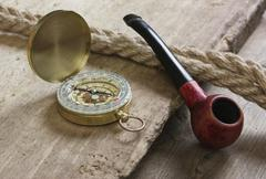 Old tobacco pipe and compass Stock Photos