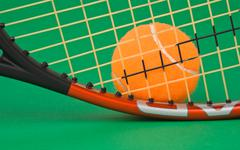 Stock Photo of tennis racket and  ball on green background