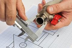Plumbing fittings in hand on drawing Stock Photos
