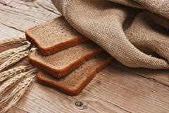 slices of rye bread and ears of corn - stock photo