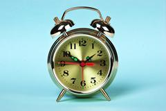 golden alarm clock on a color background - stock photo
