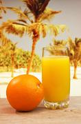 glass of orange juice on a beach - stock photo