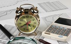 Stock Photo of gold clock and office supplies