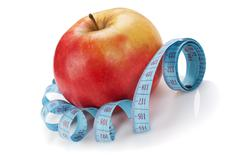 Stock Photo of blue measure tape and red apple  isolated