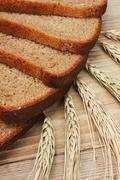 Slices of rye bread and ears of corn on a wooden table Stock Photos