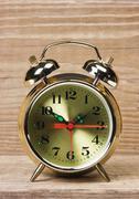 Golden alarm clock  on  wooden table Stock Photos
