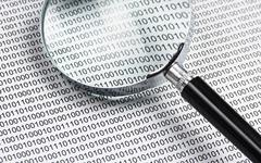 magnifying glass on a binary code - stock photo