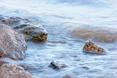 surf on rocky shore - stock photo