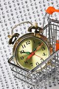alarm clock in a shopping basket - stock photo