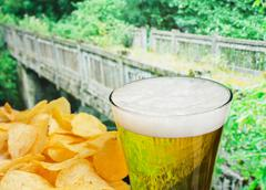glass of beer and potato chips in a landscape - stock photo