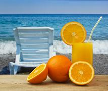 Stock Photo of glass of orange juice on a beach