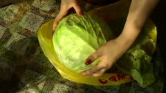 Hands of mother clear a head of cabbage for further preparation Stock Footage