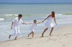 mother, father and child family running having fun at beach - stock photo