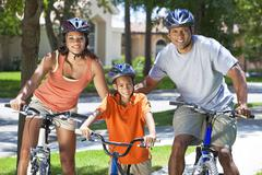african american parents with boy son riding bike - stock photo