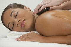 woman relaxing at health spa having hot stone treatment massage - stock photo