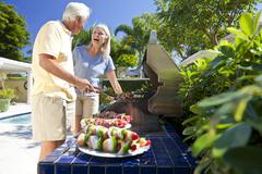 happy senior couple outside cooking on a summer barbecue - stock photo