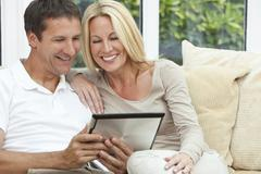 happy man & woman couple using tablet computer - stock photo
