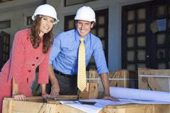 man & woman in hard hats on construction site - stock photo