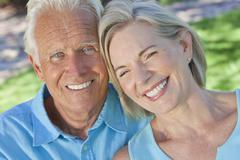 happy senior couple smiling outside in sunshine - stock photo