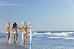 three beautiful women surfers in bikinis with surfboards at beach - stock photo