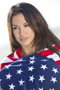 beautiful girl woman at beach in stars & stripes american flag - stock photo