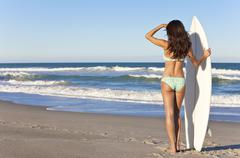 Beautiful woman surfer in bikini with surfboard at beach Stock Photos