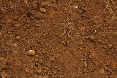 Red soil, with stones. - stock photo