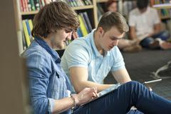 male boy students using tablet computers in library - stock photo