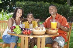 african american family eating healthy food outside - stock photo