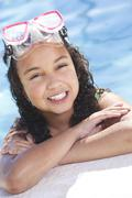 african american interracial girl child in swimming pool with goggles - stock photo
