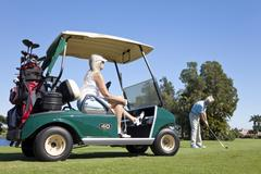 Happy senior couple playing golf with cart Stock Photos