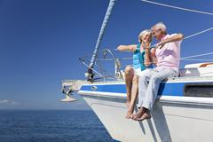 happy senior couple sitting on a sail boat - stock photo