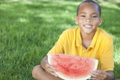 Happy african american boy child eating water melon Stock Photos