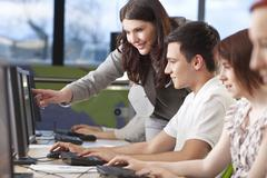 student & teacher using computers at college - stock photo