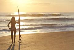 Woman surfer in bikini with surfboard at sunset beach Stock Photos