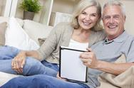 Stock Photo of happy senior man & woman couple using tablet computer
