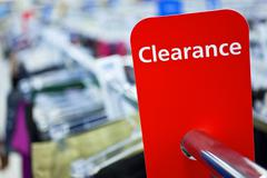 Sale clearance sign on rail in clothes shop Stock Photos