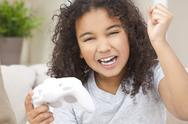Happy mixed race african american girl child playing video games Stock Photos